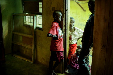 Eight year old Momoh (red t-shirt) stands in a doorway at the Interim Child Centre a children's home run by the St George Foundation. Currently 21 children live in the home, all there as a result of t...