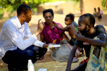 A member medical staff from the Mulanje Mission Hospital's home care team talks with Patrick Mandeule and his family during a visit to their home. Patrick has a leg tumour but while his relatives are...
