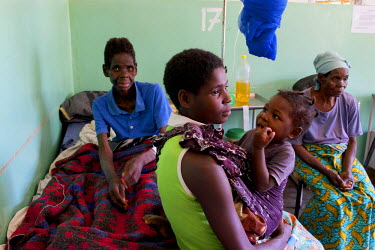 Annie Josaya, 48, sits up in her hospital bed during a family visit. She has advanced cervival cancer and receives palliative care, including symptomatic relief, at the Mulanje Mission Hospital. Pione...