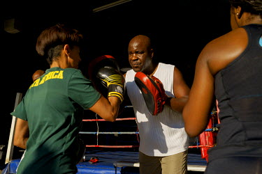 George Khosi training a woman during a corporate boxing day at the Hillbrow Boxing Club. The club relies on a small number of private and corporate clients to pay the club's bills, as much of the work...