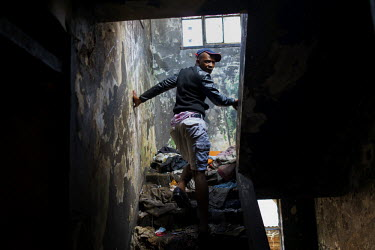 Simo on his way up to the roof a 'hijacked building' (slang that decribes an illegally occupied squat) where he lives in in Hillbrow. The building has neither electricity nor running water, and refuse...