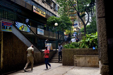 People walk a stairway, past a pawn shop, towards the entrance to the only shopping centre in Hillbrow. The district, in downtown Johannesburg, is the city's most notorious. It is overcrowded, ridden...