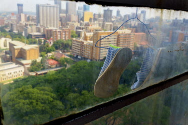 A pair of slippers hangs out of a window in Highrise, a 19-storey residential tower overlooking a park in Hillbrow, Johannesburg's most notorious neighbourhood. Once a preserve of middle-class whites...