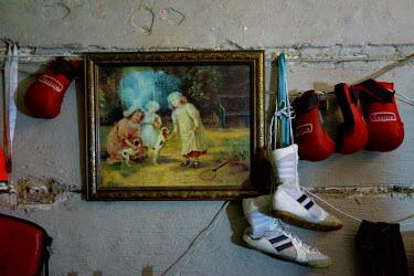 Siyakudumisa Vapi's boxing boots and pairs of child-sized boxing gloves hang next to a painting on the wall in his room. Currently living in a curtained-off space in the basement of the Hillbrow Boxin...