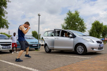 Joe Eades being coached by Julie Tshabalala, South African women's welterweight and middleweight champion, while she sits in her car eating her lunch and waiting for for an amateur boxing tournament t...