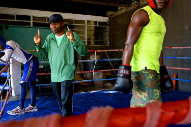 Trainer James Ike offers stern words of advice to Angel Harrison (left) and Yomi Shokunbi (right) between rounds of sparring at the Hillbrow Boxing Club. Both boxers are aspiring professionals, hoping...