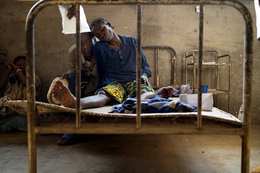 Justine Imbida, approximately 30, rests her head against her father's at a hospital in Bili. The day before, she and her younger sister were shot over the nearby border in Central African Republic (CA...