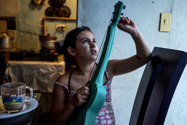 A neice of Gloria Acevedo Restrepo plays with a toy guitar, in Nuevo Occidente, a massive social housing complex, of mostly displaced or forced evicted families. 18 family members live in this 70 squa...