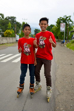 Two boys in matching T-shirts display their love of in-line skating.