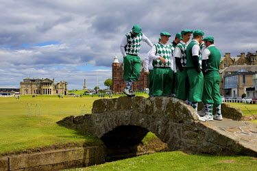 A group of tourists from Wisconsin, USA, dressed in plus fours and caps, pose on the Swilcan Bridge at the 18th hole of the Old COurse at ST Andrews. On Sundays, people are free to explore the hallowe...