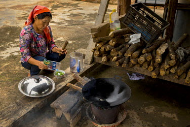 Wang Guiying, 51, prepares a meal in the yard of her home in Tuanjie Village.