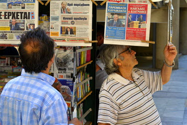 Middle aged Greek man check the latest news at a newsstand in Athens. In the leadup to the end of Greece's bailout programme from the 'troika' (30 June 2015) Greek banks were instructed to close until...