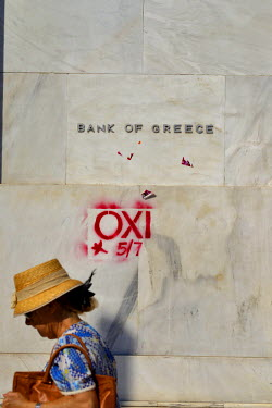 A women in the central Syntagma district of Athens walks past a branch of the Bank of Greece with a campaigning 'No' ('Oxi') vote graffiti spray-painted on the wall. A Bird in the HandIn the leadup to...
