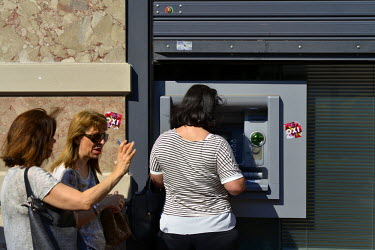 Women discuss their current situation while queueing to withdraw their money, limited to 60 Euros per day, from an ATM machine with 'No' ('Oxi') vote stickers beside it. In the leadup to the end of Gr...