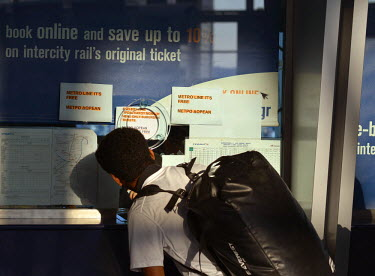A tourist asks at the train ticket booth at the Athens International Airport train station about traveling in to the city, and is told (see printed signs) that all Metro rides are free, by government...