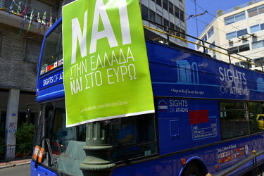 An empty tourist double-decker sightseeing bus passes behind a 'Yes' ('Nai') referendum poster in central Athens. On 26 June 2015 Greek Prime Minister Alexis Tsipras called a surprise referendum to as...