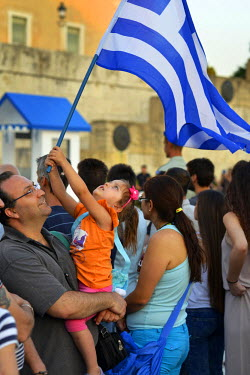 Held in her father's arms, a girl waves a Greek flag in Syntagma Square on the day before a national referendum to acceptance or reject economic reforms demanded by the country's creditors. The outcom...