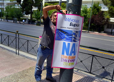 A worker staples up a vote 'Nai' ('Yes') poster to a post on the day before a national referendum to acceptance or reject economic reforms demanded by the country's creditors. The outcome could determ...