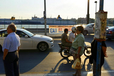 People wait at a bus stop as traffic passes the port. On the roadside a banner supports a 'No' vote on the day before a national referendum to acceptance or reject economic reforms demanded by the cou...