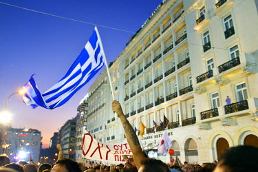 A man waves a Greek flag as a large crowd, supporting a 'No' vote, gathered in Syntagma Square on the day before a national referendum to acceptance or reject economic reforms demanded by the country'...