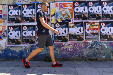 A man walking through the suburb of Kessariani, the site of a Nazi massacre of communists in 1940. Posters calling for a 'No' vote in the following day's referendum are pasted on a wall in an area tha...