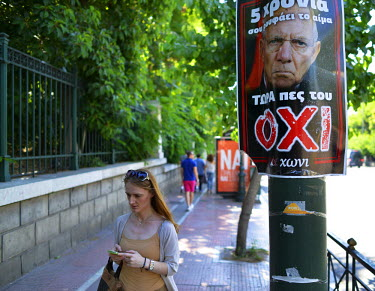 A woman walks past a vote 'No' poster featuring the widely disliked German Finance Minister, Wolfgang Schaeuble.  On 5 July 2015 Greeks voted in a referendum to acceptance or reject economic reforms d...