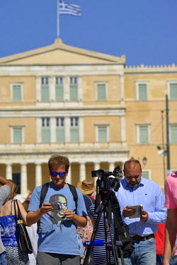 Members of the international media in Syntagma Square with the Parliament Building in background on the day before a national referendum to acceptance or reject economic reforms demanded by the countr...