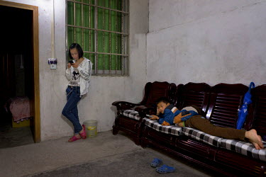 Long Yang 11 (left) plays on her mother's mobile phone as  her brother Long Pei, 10 (right) watches TV at home in Wuxi, the fast growing city that was formerly known as White Horse Village.