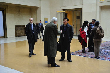 Russian and Chinese diplomats in discussion outside the Conference on Disarmament while a second Russian waits at left.  The Conference on Disarmament, established in 1979, is the only forum for natio...