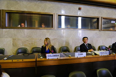 Delegates to the Conference on Disarmament from Colombia and the Democratic People's Republic of Korea (North Korea), prior to the opening of the session. Translators occupy the boxes behind. The Con...