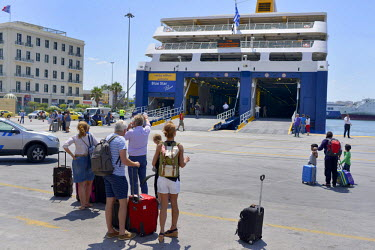 Tourists disembark from a Blue Star Lines ferry that has just docked at Athens' port of Piraeus, coming from one of the Greek islands. Tourism - a mainstay of the Greek economy - has been affected by...