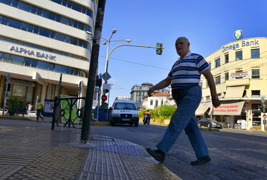 From the Alpha to the Omega; a Greek citizen crosses a main street in downtown Piraeus - Athens' port suburb - between branches of the Alpha and Omega banks, both of which remain closed for normal bus...