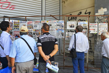 People pause at a newsstand in busy Omonia Square, in central Athens, to catch up on the latest news regarding their country's debt crisis.   On 5 July Greeks voted  'no' in a referendum which asked w...