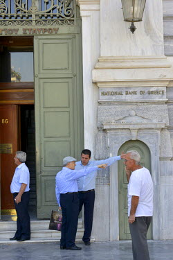 A bank employee points out directions to the ATM machines to a customer outside the National Bank of Greece, in central Athens.  Most Greek banks have been closed since the announcement of a referendu...