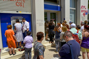 People queue to use the ATM machine and gain limited access to a bank branch in central Athens.  Most Greek banks have been closed since the announcement of a referendum on the conditions imposed by t...
