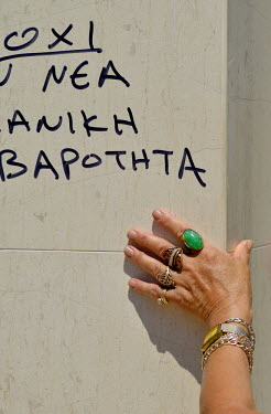 The hand of a woman wearing rings and bracelets is seen below a graffiti on the walls of a bank while she waits her turn outside a bank in central Athens.  Most Greek banks have been closed since the...