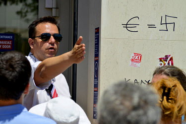 A bank employee at a branch of Eurobank in central Athens tries to calm the tempers of account holders having to queue to get inside the bank. Next to him a graffiti reads; 'Euro symbol = swastika'....