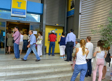 People queue both to use the ATM machine and gain limited access to a bank branch in central Athens.  Most Greek banks have been closed since the announcement of a referendum on the conditions imposed...