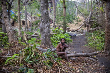 A man sits at the entrance of Yakel village. Yakel village is known for its preservation of traditional lifestyle and culture and is a tourist attraction. The village was damaged by Cyclone Pam and lo...