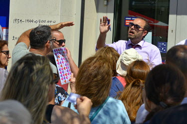 A bank employee, at a branch of Eurobank in central Athens, tries to calm the tempers of account holders having to queue to be allowed inside the bank.   Most Greek banks have been closed since the an...