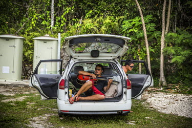 A man sits in the boot of a car, playing his guitar, while other visitors from New Zealand rest at the Matapa picnic area. Niue is mainly visited by New Zealanders since access to the island is only p...