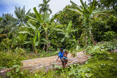 Goreti Kirua, 30, sits with her three year old son Sebilon on a log cut down, but then rejected by loggers. Kirua says: 'Foreigners forced us to sign consent forms, then they destroyed our forest.' Th...