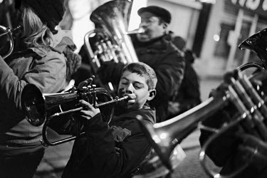 A boy plays a trumpet in a street band marching down a street in central Charleroi.