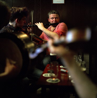 A band playing traditional Irish instruments in a bar.