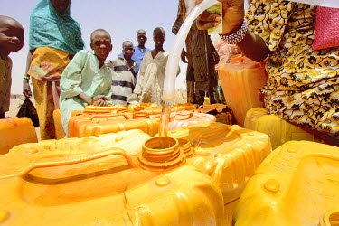 A woman fills jerry cans with water from a communal water supply. Water is precious in the Sahel and the host communities, such those of Nguel Kolo, now have to share their resources with over 100,000...