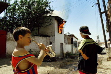 July 1999: Young Ethnic Albanian men watch as a house belonging to Roma people is burned in the divided city of Mitrovice/ Mitrovica.