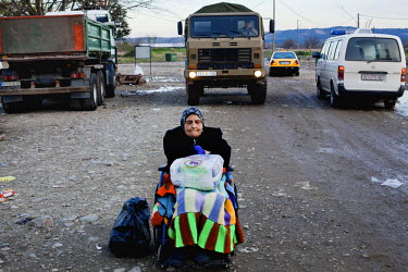 An elderly Syrian refugee sits in a wheelchair at the end of a long queue of people waiting to be registered after crossing with her family from Greece.