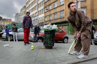 Yusuf (right) plays cricket on the main square in the Moolenbeek district of Brussels with his friends on the day after the terrorist attacks in Brussels. Molenbeek has been linked to both the Paris a...