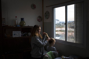 Matti Blumberg, 27, arranges one of her daughter's hair. The young single mother of three, who grew up in America, lives on the hill of Esh Kodesh, one of approximately 100 Jewish outposts in the West...