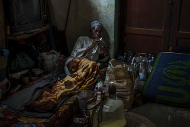 A man lies on a makeshift bed, next to his possessions and several bottles used for storing water, and listens to his radio early in the morning. His shelter is in a building within the Carnort church...